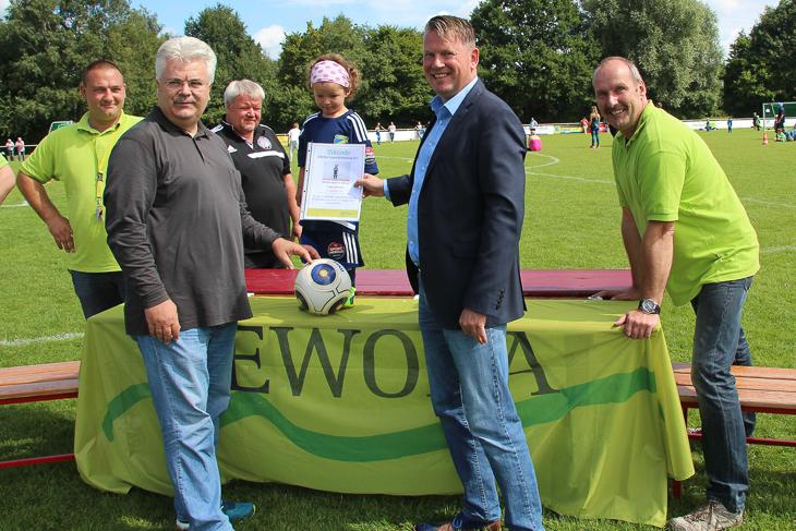 Jörn Straka von der GEWOBA (r.) und Frank Schildt aus dem Vorstand des SFL Bremerhaven (l.) überreichnten der mit 98 cm kleinsten Spielerin des Turniers, Evangeline Flint vom TuSpo Surheide, eine Urkunde und einen Ball.