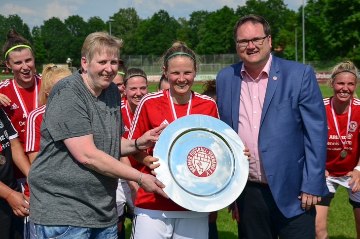 BFV-Präsident Björn Fecker (r.) und Verbandsliga-Spielleiterin Angela Franke (l.) übergaben die Meisterschale an TuS-Kapitänin Lara Möhlmann. (Foto: Olaf Lücke)