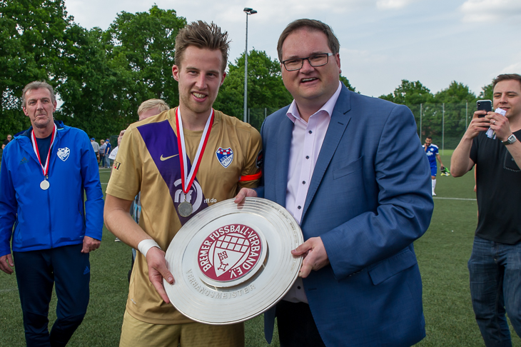 BFV-Präsident Björn Fecker (r.) übergab die Meisterschale an Brinkums Kapitän Jannik Bender. (Foto : Oliver Baumgart)