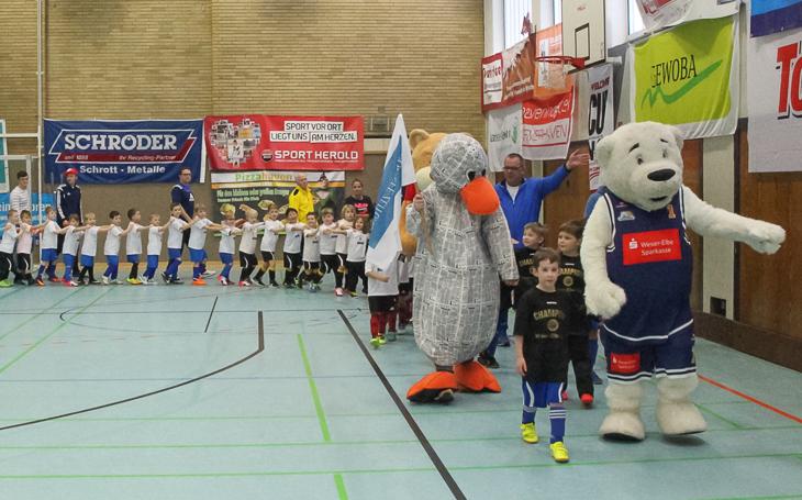 Die unseren G-Junioren marschieren in die Walter-Kolb-Halle ein. Angeführt werden sie von den Maskottchen der Nordsee-Zeitung und der Eisbären Bremerhaven.