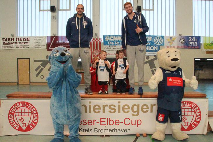 Die Großen ehren die Kleinen: Carl Baptiste (2,08 m), Lennov Schönberger (0,97 m), Evangeline Flint (1,01 m) und Geoffrey Groselle (2,13 m, v.l.) bei der Siegerehrung der G-Junioren, die die Basketballprofis der Eisbären Bremerhaven vornahmen. (Fotos: Ralf Krönke)