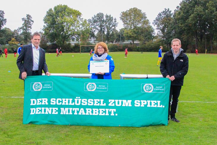 DFB-Ehrenamtspreisträgerin Bettina Henze (Mitte) erhält ihre Geschenke von BFV-Vizepräsident Michael Grell (links) und Gerrit Süßmann aus dem Ehrenamtsausschuss (rechts). (Foto: Ralf Krönke)