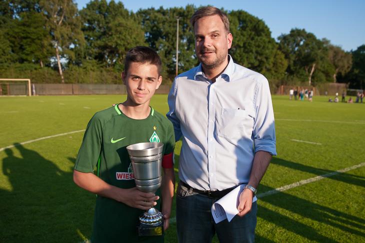 Werder-Kapitän Emre Karagöz (l.) mit dem Pokal, den Sebastian Störer aus dem Verbandsjugendausschuss übergab. (Foto: Oliver Baumgart)