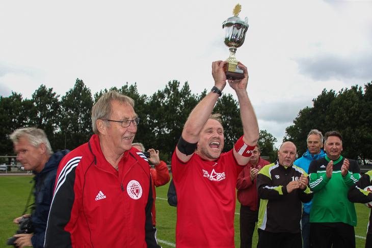 Markus Ahlfeld, Kapitän der Ü 40-Senioren des ESC Geestemünde, stemmt den Pokal in den Himmel, den ihm Jürgen Türk (l.) überreichte. (Foto: Ralf Krönke)