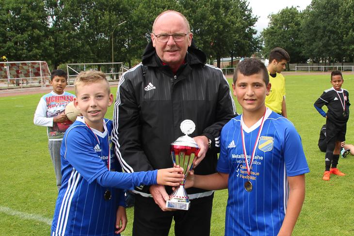 Kreisvorsitzender Axel Zielinski (m.) übergabe den Pokal der D-Junioren an den TuSpo Surheide. (Foto: Ralf Krönke)