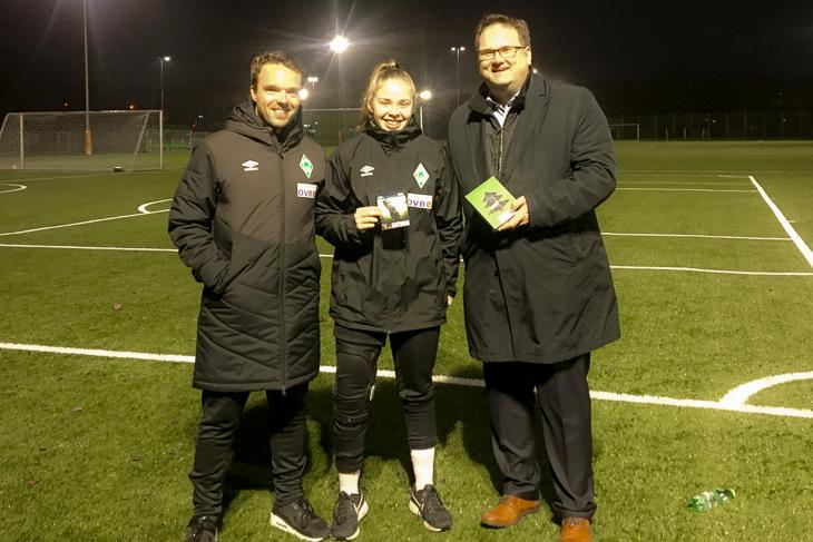 BFV-Präsident Björn Fecker (rechts) überreicht der Sportverletzten Kim-Sophie Baade (mitte) ein Trostgeschenk. Werders Frauen U17-Trainer Alexander Kluge (links) meldete die Verletzung dem Verband.
